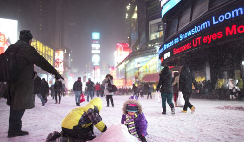 Children make a snow pile in Times Square, during a snowstorm on Jan. 2, 2014 in New York. /AP