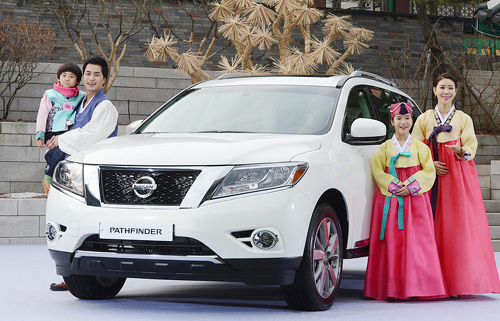 Models pose with Nissans Pathfinder SUV at a hotel in Seoul on Tuesday. /Newsis