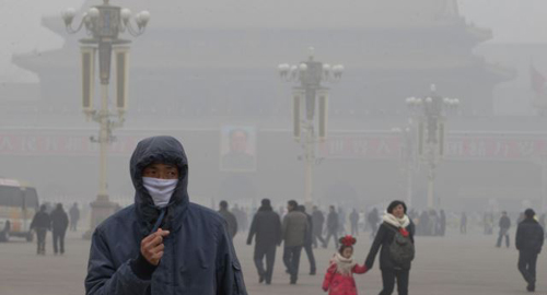 A man wears a mask on Tiananmen Square in thick haze in Beijing. /AP