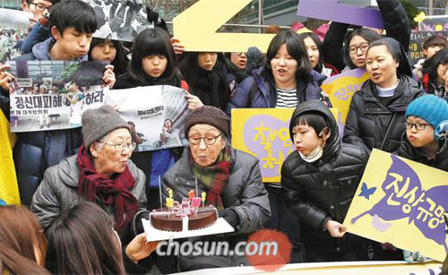 Former sex slaves, Kil Won-ok (left) and Kim Bok-dong, blow out candles with volunteers to mark the 22nd anniversary of protests in front of the Japanese Embassy in Seoul on Wednesday.