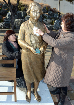 Officials wipe a statue honoring former sex slaves for the Japanese Imperial Army in Geoje, South Gyeongsang Province on Thursday, a day before its unveiling. /Newsis