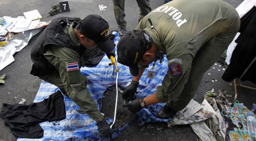 Thai policemen check the scene following an explosion near a camp of anti-government protesters at the Victory monument in central Bangkok on Jan. 19, 2014. /Reuters