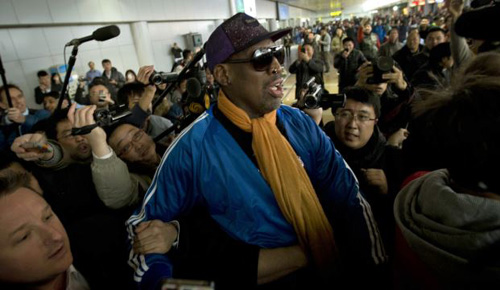 Former NBA basketball player Dennis Rodman is followed by journalists as he arrives at the Capital International Airport in Beijing from Pyongyang on Jan. 13, 2014. /AP