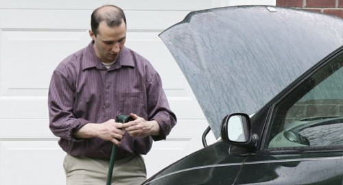 James Everett Dutschke works on his minivan in his driveway in Tupelo, Mississippi in April 2013. /Reuters