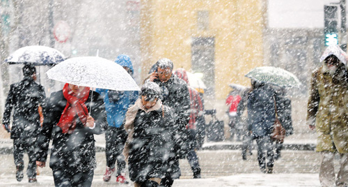 Pedestrians walk through snow in Gwanghwamun on Monday.