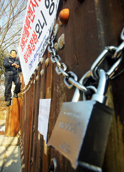 A staffer posts a notice of the temporary closure of a wetland park near Sihwa Lake, a habitat for migratory birds, in Ansan, Gyeonggi Province on Wednesday. /Newsis