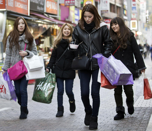 Foreign tourists walk in the shopping district of Myeong-dong, Seoul on Jan. 15.