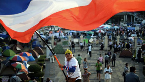 A Thai anti-government protester waves a national flag during ongoing rallies at a protest site at Victory Monument in downtown Bangkok on Jan. 24, 2014. /AFP