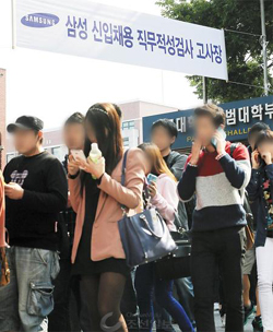 Applicants leave a high school in Seoul after taking a job aptitude test by the Samsung Group on Oct. 13, 2013.