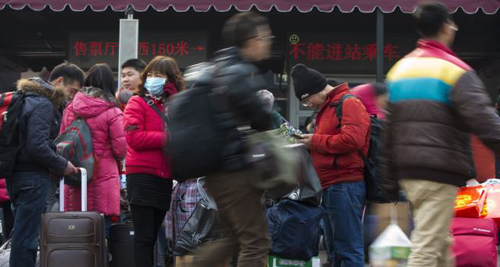Passengers carry their belongings while arriving at the Beijing railway station in Beijing on Jan. 19, 2014. /AP