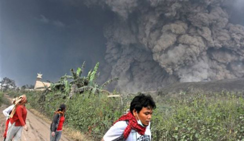 Villagers flee as Mount Sinabung releases pyroclastic flows during an eruption in Namantaran, North Sumatr on Feb. 1, 2014. /AP