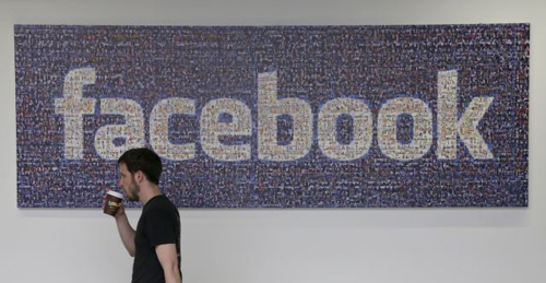 Facebook employee walks past a sign at company headquarters in Menlo Park, California./AP