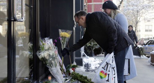 A couple adds to the flowers placed outside the apartment building of actor Phillip Seymour Hoffman in New York on Feb. 4, 2014. /AP