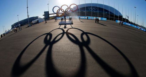 The Olympic rings are cast in shadow as the sun sets behind the Bolshoy Ice Palace as preparations continue at the Olympic Park for the 2014 Winter Olympics in Sochi, Russia on Feb. 3, 2014. /Reuters