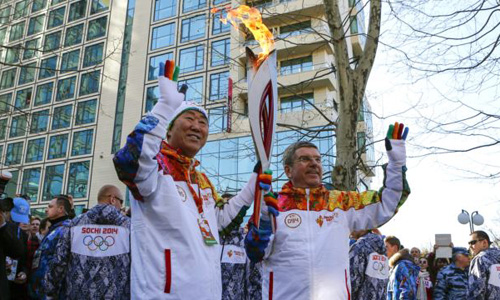 IOC President Thomas Bach (right) hands over the Olympic torch to United Nations Secretary-General Ban Ki-moon as the torch relay arrives in Sochi, ahead of the 2014 Winter Olympics, on Feb. 6, 2014 in Russia. /AP