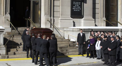 Mimi ODonnell, former partner of actor Phillip Seymour Hoffman, holds their daughter Willa (in purple) next to their son Cooper as the casket arrives for Hoffmans funeral in the Manhattan borough of New York on Feb. 7, 2014. /Reuters