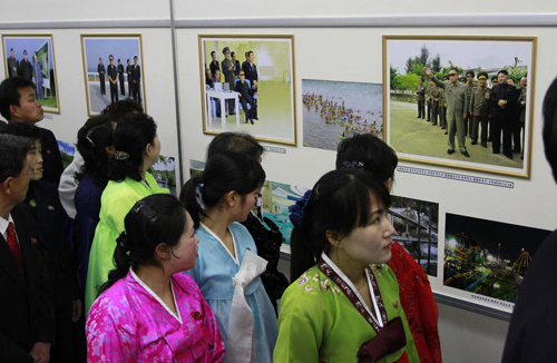 Visitors look at a photo exhibition on the occasion of the Feb. 16, birthday of former North Korean leader Kim Jong-il in Pyongyang on Tuesday. /AP-Newsis