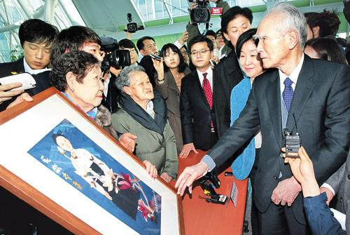 Former Japanese Prime Minister Tomiichi Murayama (right) receives a painting by the late Kim Sun-duk, one of the women who were forced into sexual slavery for the Japanese Imperial Army, during a visit to an exhibition of artworks by the former