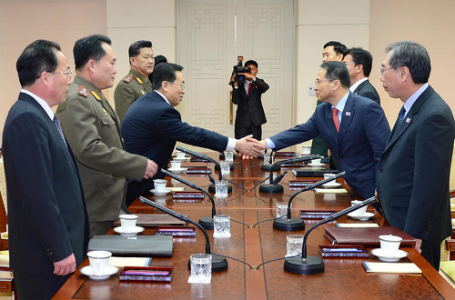 South and North Korean delegates shake hands before talks at the border truce village of Panmunjom on Wednesday.