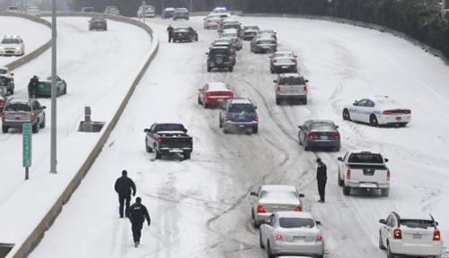 Charlotte Mecklenburg Police Officers work to assist motorists as they attempt to drive up a hill that is covered in snow in Charlotte, North Carolina on Feb. 12, 2014. /Reuters