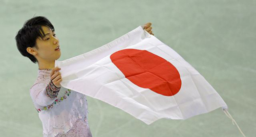 Yuzuru Hanyu of Japan poses with the national flag after he placed first in the mens free skate figure skating final following the flower ceremony at the Iceberg Skating Palace during the 2014 Winter Olympics on Feb. 14, 2014 in Sochi, Russia. /AP