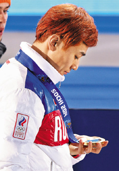 Viktor Ahn looks at his gold medal after the awards ceremony for the mens 1,500-m race in short track skating at the 2014 Winter Olympics in Sochi, Russia on Saturday. /Newsis