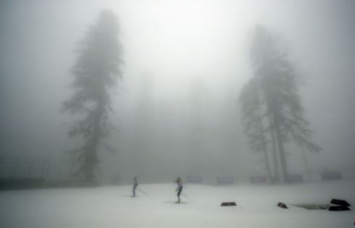 Athletes train as fog enshrouds the course of the mens biathlon 15k mass-start, at the 2014 Winter Olympics on Feb. 17, 2014. /AP