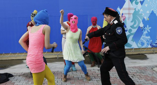 Members of the punk group Pussy Riot, including Nadezhda Tolokonnikova in the blue balaclava and Maria Alekhina in the pink balaclava, are attacked by Cossack militia in Sochi, Russia on Feb. 19, 2014. /AP