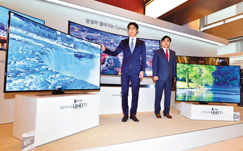 National football coach Hong Myung-bo (left) attends an event to unveil curved UHD TVs by Samsung Electronics in Seoul on Thursday.