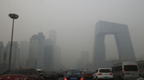 Cars travel on a road amid heavy haze in Beijing on Feb. 21, 2014. /Reuters