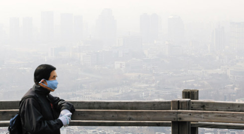 A man wearing a mask looks at downtown Seoul from Mt. Nam on Sunday.