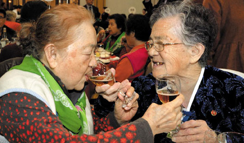 Sisters who separated during the Korean War offer drinks to each other during a family reunion at Mt. Kumgang resort in North Korea on Monday. /Newsis