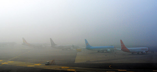 Airplanes wait to receive the green light for takeoff at Gimpo Airport in Seoul on Tuesday morning as thick haze grounded flights. /News 1