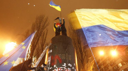 People fly Ukrainian and European Union flags following the toppling by protesters of a statue of Soviet state founder Vladimir Lenin in Kyiv on Dec. 8, 2013. /Reuters