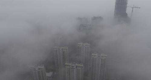 Buildings are seen shrouded in heavy haze at Qingdao development zone, Shandong province on Feb. 25, 2014. /Reuters