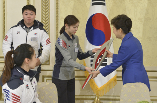 Kim Yu-na presents President Park Geun-hye with a replica Olympic torch in Cheong Wa Dae on Wednesday.
