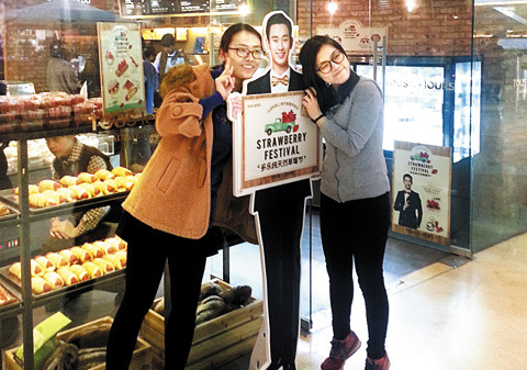 Chinese women pose with a life-sized cutout of Kim Soo-hyun in front of a Tous les Jours bakery in Beijing. /Courtesy of CJ Foodville