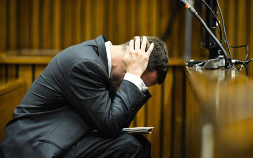 Oscar Pistorius cradles his head in his hands in court on the fifth day of his trial at the high court in Pretoria, South Africa on March 7, 2014. /AP