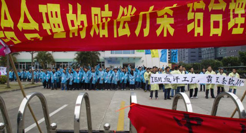 IBM workers shout slogans and hold banners as they protest at an IBM factory in Shenzhen, Guangdong Province on March 7, 2014. /Reuters