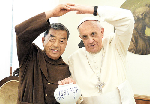 Pope Francis poses with Oh Woong-jin, a priest who founded the Flower Village, during Oh's visit to the Vatican in August 2013. /Courtesy of Flower Village