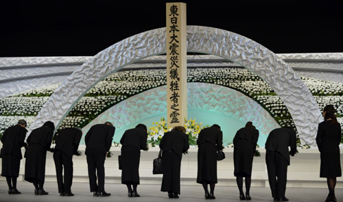 Relatives of victims of the March 11, 2011 earthquake and tsunami bow to the altar as they offer chrysanthemums for the victims at the national memorial service in Tokyo on March 11, 2014. /Reuters