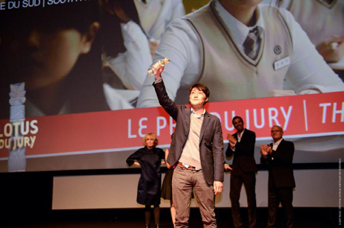 Director Lee Su-jin hoists his trophy after receiving the jury prize award at the Deauville Asian Film Festival in France on Monday. /Courtesy of Movie Collage