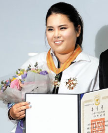 World No. 1 golfer Park In-bee holds a certificate showing her receipt of the Maengho Medal, the second-highest Order of Sports Merit, at the National Museum of Korean Contemporary History in Seoul on Tuesday.