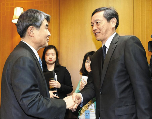 Japanese Vice Foreign Minister Akitaka Saiki (right) shakes hands with his Korean counterpart Cho Tae-yong at the Foreign Ministry on Wednesday.