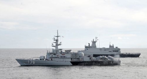 A Royal Malaysian Navys missile corvette and an offshore patrol vessel are seen during a search and rescue operation for the missing Malaysia Airliner over the Straits of Malacca, Malaysia on March 13, 2014. /AP