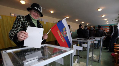 A woman holds a Russian flag as she casts her ballot during the referendum on the status of Ukraines Crimea region at a polling station in Bakhchisaray on March 16, 2014. /Reuters