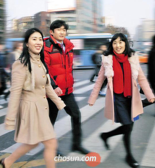 North Korean defectors walk across a crosswalk in Seoul.