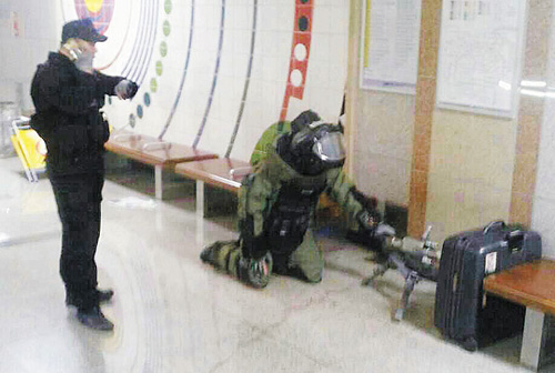 An explosive disposal squad member checks a bag suspected of containing a bomb at Gangnam District Office Station in Seoul on Monday. /Courtesy of the Seoul Metropolitan Police Agency