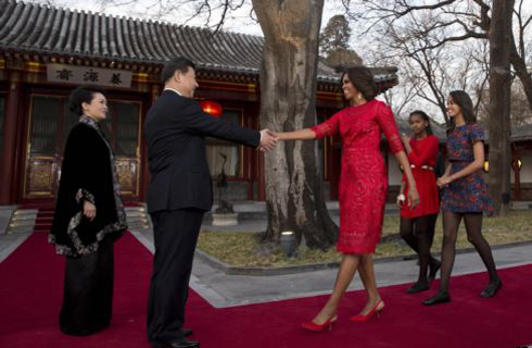 U.S. first lady Michelle Obama, followed by her daughters Malia and Sasha, is greeted by Chinese President Xi Jinping and his wife Peng Liyuan at the Diaoyutai State guest house in Beijing on March 21, 2014. /AP