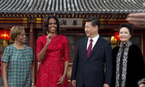 U.S. first lady Michelle Obama, her mother Marian Robinson (left), share a light moment with Chinese President Xi Jinping, and his wife Peng Liyuan (right) after a photograph session at the Diaoyutai State guest house in Beijing on March 21, 2014. /Reuters